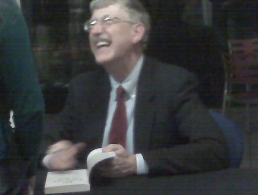 Francis Collins signs a copy of his book